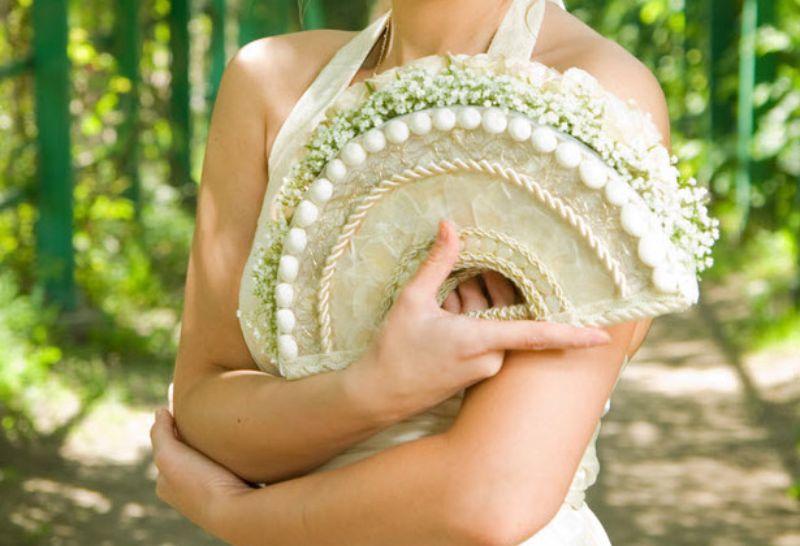 Mẫu hoa hình quạt được cố định bởi chiếc quạt nứa, tre mỏng điểm tô những cành hoa baby trắng
