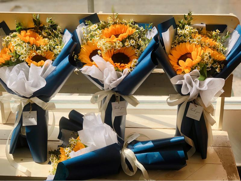 4 bó hoa hướng dương màu vàng trong giấy gói xanh