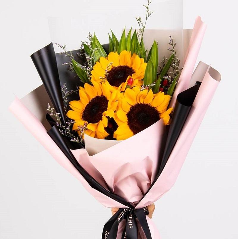 bó hoa hướng dương 3 bông màu vàng trong giấy gói hồng đen đơn giản