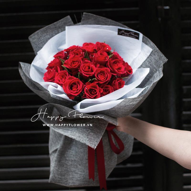 bó hoa hồng đỏ rực rỡ với giấy gói xám