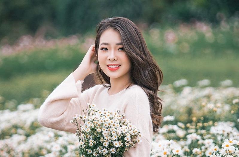Nữ sinh chụp kỷ yếu cùng hoa cúc họa mi trắng