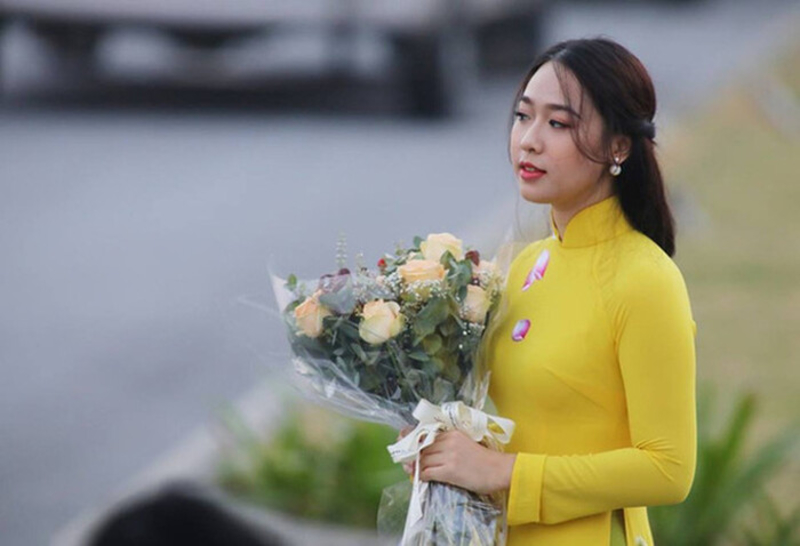 nữ sinh cầm trên tay bó hoa hồng vàng