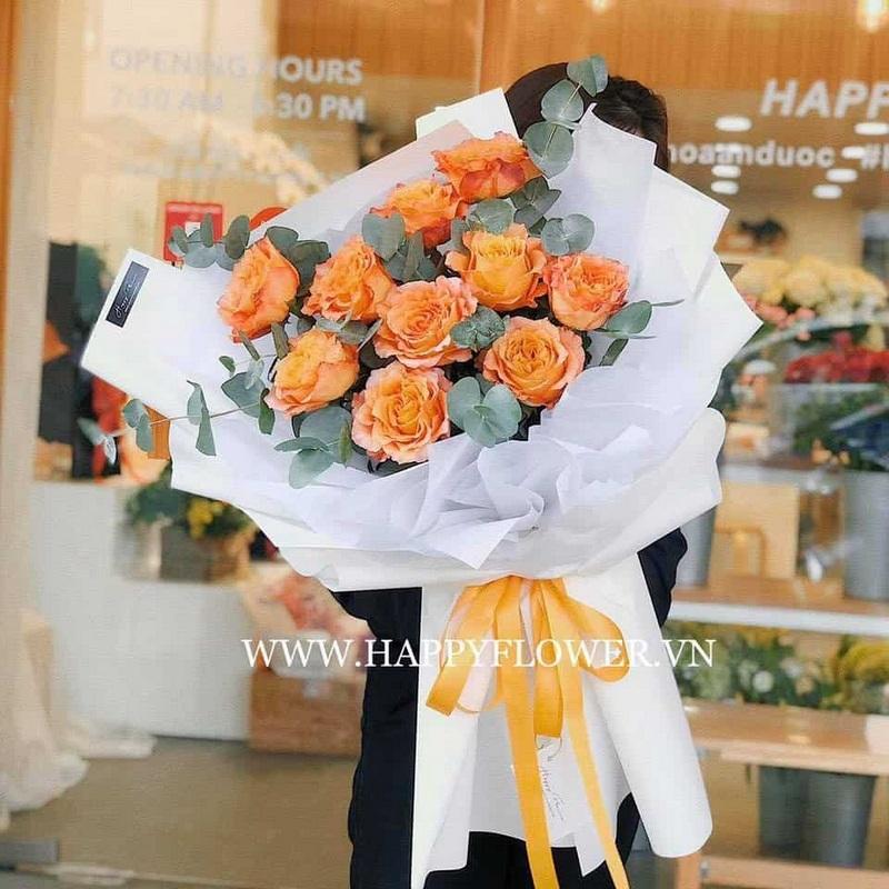 bó hoa hồng cam với giấy gói trắng