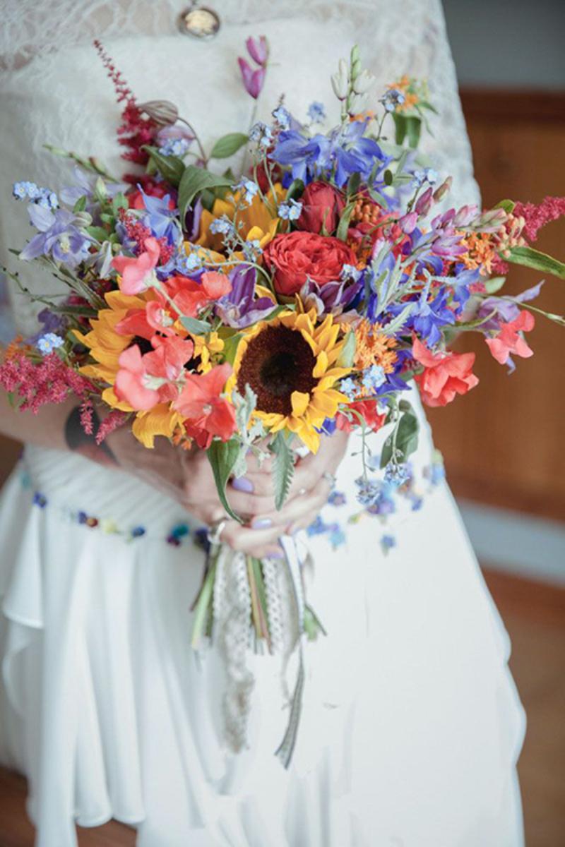 bó hoa cầm tay rực rỡ sắc màu cùng với hoa hướng dương