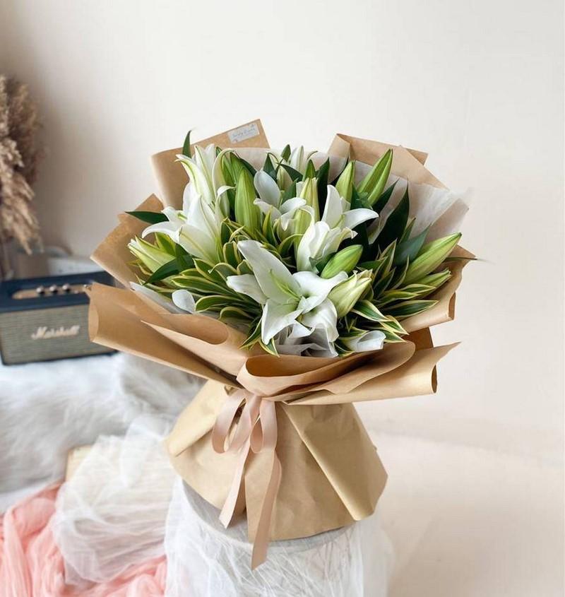 bó hoa loa kèn màu trắng trong giấy gói nâu